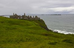 Die schattenhaften Ruinen der mittelalterlichen Iren Dunluce ziehen sich auf die Klippenoberseite zurück, die den Atlantik in Irl Stockfotografie