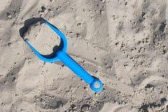 Die Schaufel der blaue Kinder im Sandkasten Lizenzfreie Stockbilder