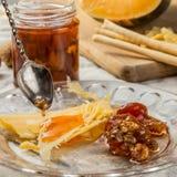 Die Scheiben des Käses mit Confiture und Walnüssen auf der Glasplatte Lizenzfreies Stockfoto