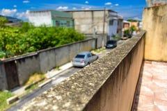 Die schimmelige Wand und die undeutliche Straße mit Autos und Wohnhäusern in Bangu-Nachbarschaft, die Westzone von Rio de Janeiro Stockbild