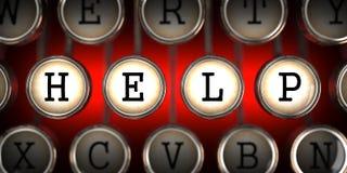 Die Schlüssel der alten Schreibmaschine mit Hilfsslogan. Lizenzfreie Stockfotografie