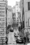Die schmalen alten Straßen von altem Rom zwischen den Häusern mit Treppe und den Touristen, die durch es Anziehungskräfte betrach Stockfotos