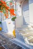 Die schmalen Straßen mit blauen Balkonen, Treppe, weißen Häusern und Blumen im schönen Dorf in Griechenland Schön Lizenzfreies Stockbild