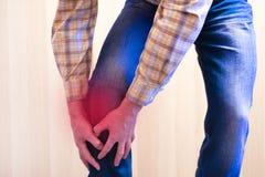 Die Schmerz des roten Hintergrundes Der Mann ergriff sein Knie in einem Sitz von Schmerz r lizenzfreies stockbild