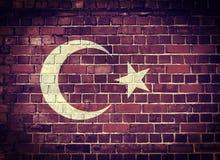 Die Schmutz-Türkei-Flagge auf einer Backsteinmauer Stockfotografie