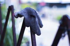 Die schmutzigen Handschuhe der Arbeitskraft, die am Zaun h?ngen, um zu trocknen, Baustelle lizenzfreie stockbilder