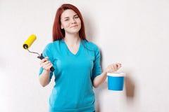 Die schöne junge Frau in der verursachenden Kleidung das Ergebnis der Arbeit genießend hat sie das Malen einer Wand getan Stockbilder