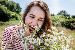 Die schöne junge Frau, die genießt, Kamillenfeld essend, blüht zum Spaß Lizenzfreies Stockfoto