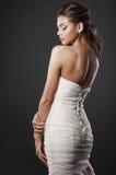 Die schöne junge Frau in einem Hochzeitskleid Lizenzfreie Stockfotos