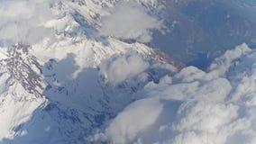 Die schneebedeckten Bergspitzen der Alpen und die weißen Wolken stock footage
