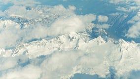 Die schneebedeckten Bergspitzen und die Wolken der Alpen an einem sonnigen Tag stock footage