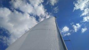 Die schneeweißen Segel der Yacht vor dem hintergrund des hellen blauen Himmels und der weißen Wolken lizenzfreies stockfoto