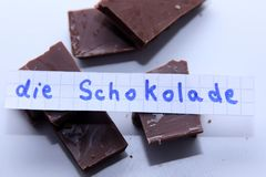 Die Schokolade, German word on a white note for English chocolate. Learn new language, German word for the English Chocolate written on a note near some Stock Image