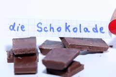 Die Schokolade, German word on a white note for English chocolate. Learn new language, German word for the English Chocolate written on a note near some Stock Photography