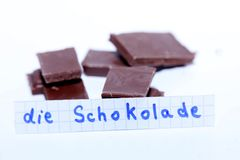 Die Schokolade, German word on a white note for English chocolate. Learn new language, German word for the English Chocolate written on a note near some Stock Photo