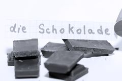 Die Schokolade, German word on a white note for English chocolate. Learn new language, German word for the English Chocolate written on a note near some Royalty Free Stock Photo