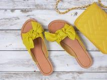 Die Schuhe der Frauen färben lederne Sandalen mit geknotetem Bogen gelb Modeausstattung, Frühjahr-Sommer Kollektion Fahrwerkbeine lizenzfreie stockbilder