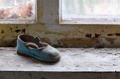 Die Schuhe der Kinder auf Fensterbrett in verlassenem Kindergarten in zerstörtem Dorf Kopachi Tschornobyl der NPP-Entfremdungszon stockbild