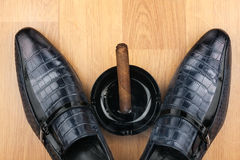 Die Schuhe der klassischen Männer, Aschenbecher und dampfende Zigarre auf dem hölzernen flo Lizenzfreie Stockfotos