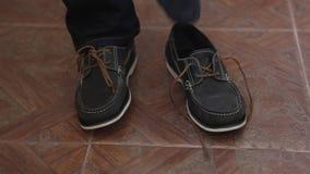 Die Schuhe der Männer, Mann schnürend ist ein Schuh vor einem Ausgang stock video footage