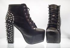 Die Schuhe der schwarzen Frauen mit Bolzen auf einem weißen Hintergrund lizenzfreie stockfotografie