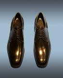 Die Schuhe der schwarzen Männer lokalisiert auf Blau Lizenzfreies Stockbild