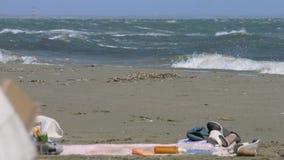 Die Schuhe der Touristen, Kleidung verlassen auf Strand, kaltes stürmisches Wetter, Hurrikan stock footage