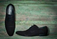 Die Schuhe des Mannes auf hölzernem Hintergrund Lizenzfreie Stockfotos
