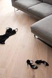 Die Schuhe und die Kleidung der Frauen, die vor einem Sofa liegen Lizenzfreie Stockfotos