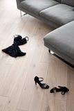 Die Schuhe und die Kleidung der Frauen, die vor einem Sofa liegen Stockfotos