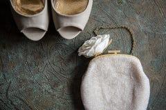 Die Schuhe und die Kupplung der Hochzeitsfrauen auf Messingbehälter mit einer Verzierung Stockfotos