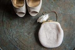 Die Schuhe und die Kupplung der Hochzeitsfrauen auf Messingbehälter mit einer Verzierung Lizenzfreies Stockfoto