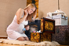 Die schwangere Frau, die Fall mit Schätzchen untersucht, kleidet Stockfotos
