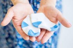 Die schwangere Frau, die in ihren Händen hält, scherzen Socken stockbild