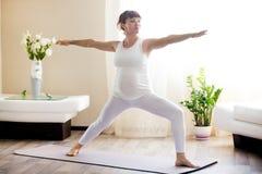 Die schwangere Frau, die Yoga des Kriegers zwei tut, werfen zu Hause auf Lizenzfreie Stockfotos