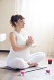 Die schwangere Frau, die in Yoga sukhasana meditiert, werfen zu Hause auf Stockbilder
