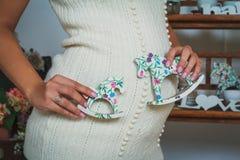 Die schwangere Frau, die zwei Pferdspielzeuge hält, nähern sich ihrem Bauch Lizenzfreie Stockbilder