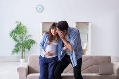 Die schwangere Frau mit Ehemann zu Hause Stockfotos