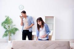 Die schwangere Frau mit Ehemann zu Hause Lizenzfreies Stockfoto