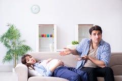 Die schwangere Frau mit Ehemann zu Hause Stockfotografie