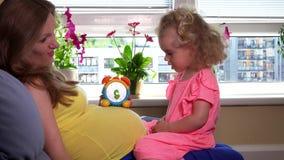 Die schwangere Mutter, die ihr nette kleine Tochtermädchenvolle stunde beibringt, nummeriert stock video