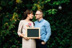 Die schwangeren glücklichen stilvollen Paare erwartend, die eine leere Holzkohle halten, verschalen Sie Lizenzfreie Stockfotos