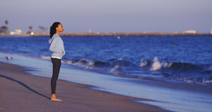 Die schwarze Frau, die den Meerblick bis Wellen genießt, kommen Lizenzfreie Stockfotografie