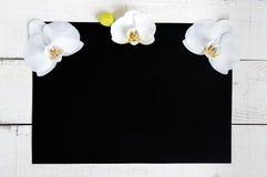 Die schwarze Größe des Rechtecks A4 und ein weißer hölzerner Hintergrund verziert mit weißen Orchideenblumen Lizenzfreies Stockbild