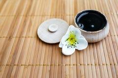Die schwarze Substanz in einem hölzernen Glas auf einem Hintergrund des Bambusses Stockbild