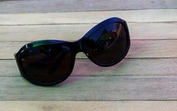Die schwarzen Gläser, die auf einem Holztisch stillstehen Stockfotografie
