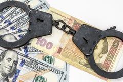 Die schwarzen Metallhandschellen liegen auf 100 Dollarscheinen Lizenzfreie Stockfotografie