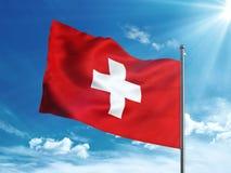 Die Schweiz fahnenschwenkend im blauen Himmel Stockfotografie