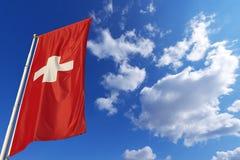 Die Schweiz-Flagge im blauen Himmel Stockfotos