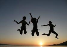 Die Schwestern springend in Sonnenuntergang Stockfotos